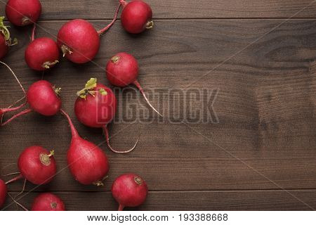 fresh red radishes on the brown table. red radishes on the wooden background. fresh red radishes for healthy diet. red radishes with copy space