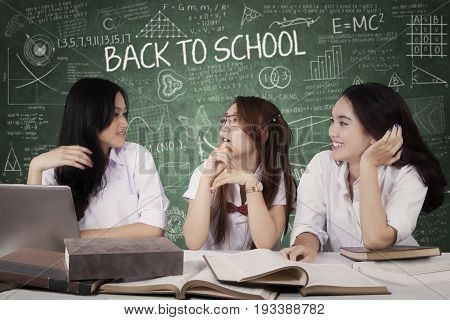 Concept of Back to School. Group of three beautiful high school students talking in the classroom with book on the table and a text of Back to School on the chalkboard