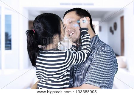 Picture of little girl drawing a star on a face of her father while sitting in the living room