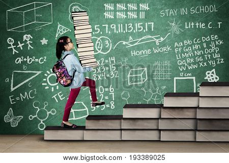 Nerdy female elementary school student holding a stack of textbooks on the stair with scribble on the chalkboard