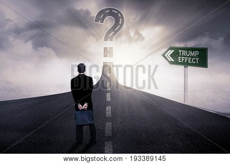 Image of a male entrepreneur standing on the road with Trump Effect word on the signpost and a big question mark