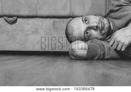 Depression. Depressed and lonely man lying on the floor of his home. Black and white. Sadness. Loneliness.