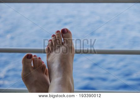Woman's feet toes painted with pink nail varnish resting on the railings of a cruise ship with sea background