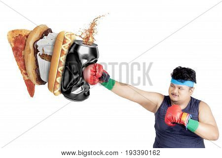Diet concept. Portrait of a young overweight man wearing sportswear and hitting fast foods: a can of soft drink hot dog cupcake donut and pizza. Isolated on white background