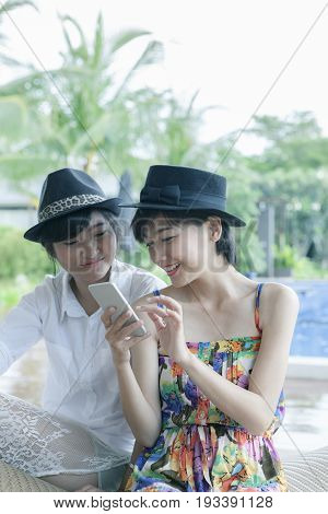 beautiful asian younger woman toothy smiling face and playing on smart phone screen