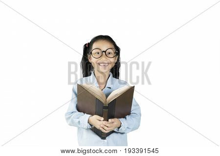Smiling schoolgirl wearing glasses holding a textbook while looking at camera isolated on white background