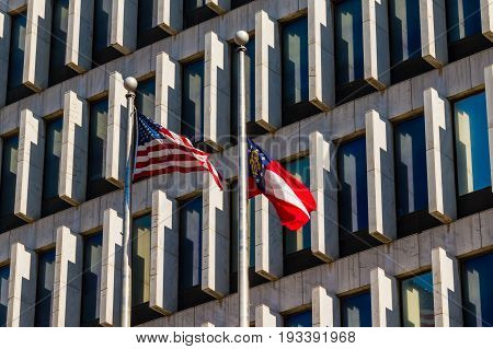 The flags of USA and Georgia on the background of facade of the office building