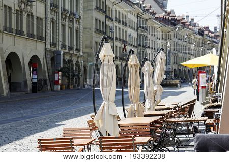 Bern Switzerland - April 20 2017: The outdoor seating restaurant has set the tables and chairs on a cobbled sidewalk in anticipation of guests. There are also umbrellas that are not yet spread