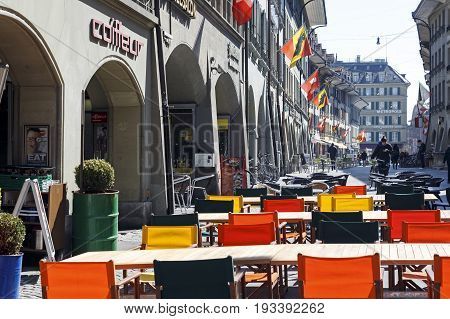 Bern Switzerland - April 21 2017: The outdoor seating restaurant has set rectangular tables and colorful chairs on a sidewalk in anticipation of guests. Several people can be seen in a distance