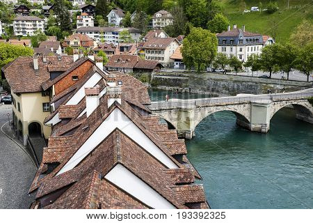 Bern Switzerland - April 17 2017: Roofs and buildings of the old town situated on the banks of the river Aare and The Untertorbruecke (Lower Gate Bridge) which is a stone arch bridge over river