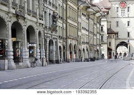 Bern Switzerland - April 17 2017: Decorative historic buildings and arcades along a cobbled street with visible tram rails and in the background the clock tower it is the center of the old town.