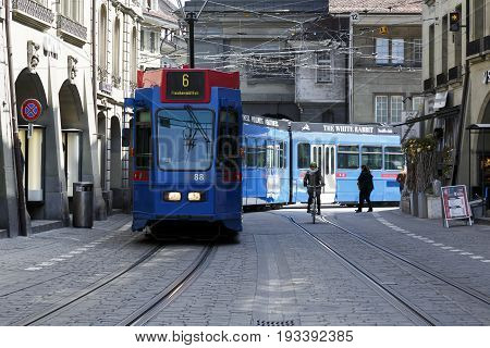 Bern Switzerland - April 20 2017: The blue tram turns from one street to the other in the old town. Along the tracks a cyclist and other people can be seen.