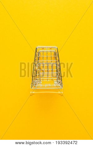top view of shopping trolley. shopping trolley on yellow background. shopping trolley with some copy space. shopping trolley with yellow handle