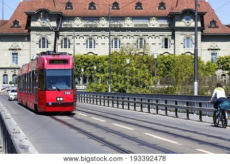 Bern Switzerland - April 21 2017: The red tram on the bridge against the background of a building of casino that in fact it is a concert house and it houses a well-known restaurant.