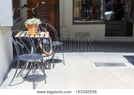 Bern Switzerland - April 20 2017: The table on which stands a flower pot and lie leaflets advertising nearby services. Two chairs a parked bike and a shop window can also be seen
