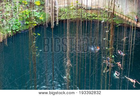 Chichen Itza Mexico - April 18 2016: Tourists bathing in the Ik Kil sinkhole