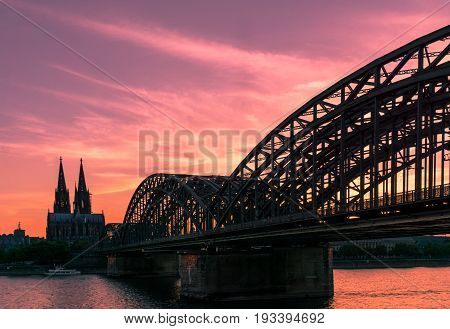 View on the Cologne Cathedral (UNESCO World Heritage) and the Hohenzollern Bridge (to cross the River Rhine in the German City of Cologne) in the Evening Light.  In Cologne, Germany 2017 The Cologne Cathedral is the greatest tourist attraction in Cologne.