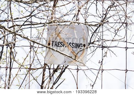 Old And Weathered No Trespassing Sign Posted To Wire Fence, Safety Concept
