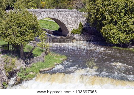 Old Stone Bridge Across A River And Waterfall In A Natural Park Area