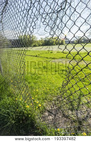 Person-sized Hole Cut Into Chain Link Fence Enclosure Around Grassy Yard