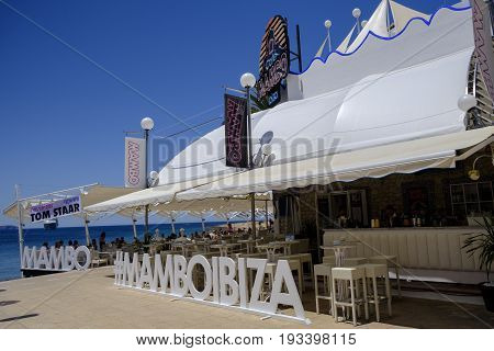 SAN ANTONIO IBIZA SPAIN - 13 JUNE 2017 - Tourists enjoying a meal in the daytime at popular Cafe Mambo Ibiza. Banner sign advertising an event for the DJ Tom Staar.