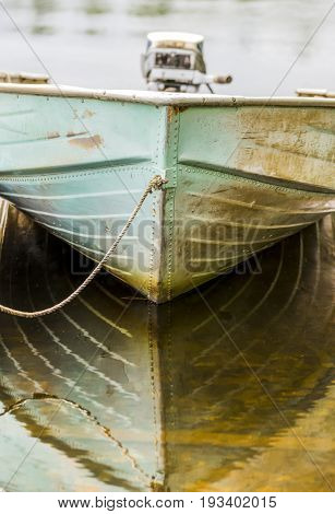 Low view of the bow of a metal one man boat aqua faded color and rust rope tied off to dock