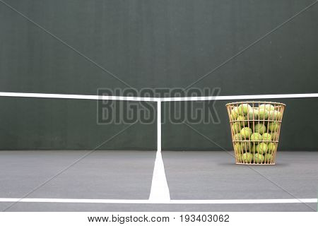 Basket of tennis balls and tennis pratice wall