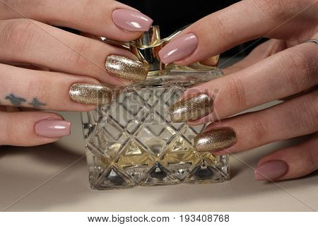 Beautiful Design Of Manicure On A Background Of A Bottle Of Perfume