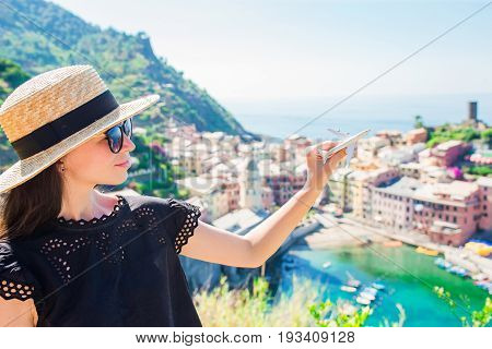 Young beautiful girl making with hands heart shape on the old coastal town background of Vernazza
