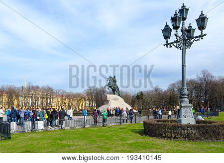 SAINT PETERSBURG RUSSIA - MAY 1 2017: Unknown tourists are at monument to Peter Great (Bronze Horseman) on Senate Square St. Petersburg Russia