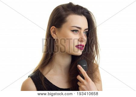 close up potrait of beautiful brunette with make up singing a karaoke with microphone