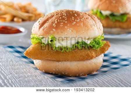A delicious crispy homemade fish sandwich with lettuce and tartar sauce.