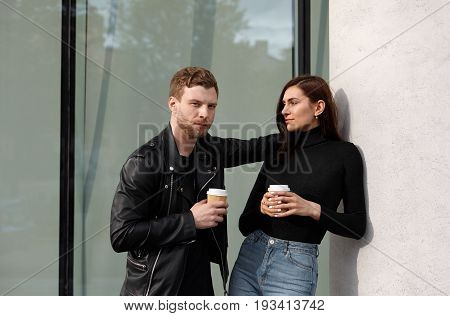 People relationships and modern urban lifestyle concept. Isolated shot of handsome young man with stubble talking to pretty girl while drinking takeaway coffee out of papercups on their first date