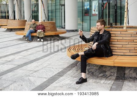 Outdoor shot of confident fashionable narcissistic European student with stubble sitting on bench in urban setting and holding his mobile phone taking selfie dressed in black trendy clothing