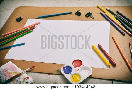 Blank empty sketch paper with pencils painting brush colour tray of white yellow blue red green and black clips over cork board for text decoration in art class in Vintage old style