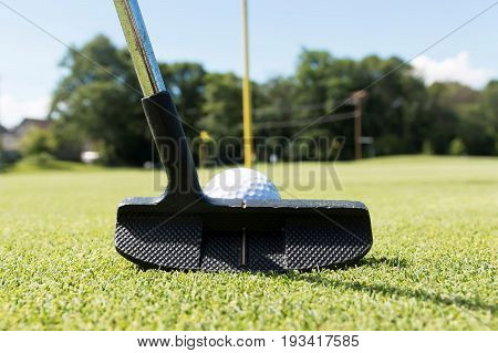 Close up view of a golf putting club with a white golf ball in front of it lining up a put toward the yellow flag pin.