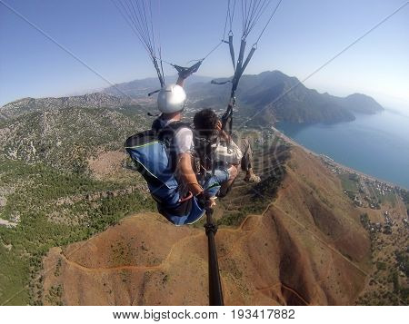 Two people are flying on a paraglider in the sky above sea