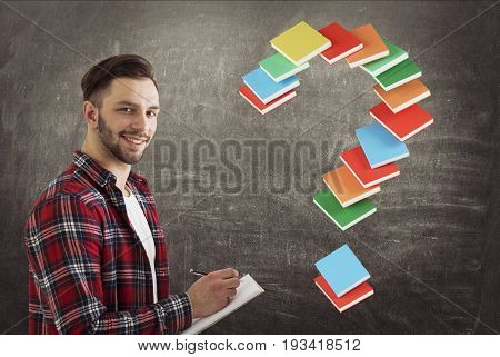 Side view of a cheerful young man holding a notebook and a pen and standing near a blackboard with a question mark made of book. Toned image