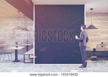 Man in a wooden and dark gray wall cafe interior with a large black wall fragment in the center and old oil lamps on square wooden tables. 3d rendering mock up toned image