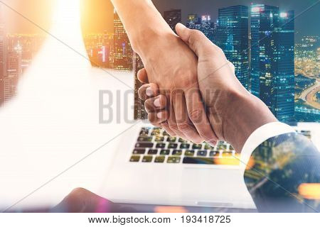 Close up of an African American man and a woman shaking hands. Office background. Night cityscape. Concept of partnership. Toned image.
