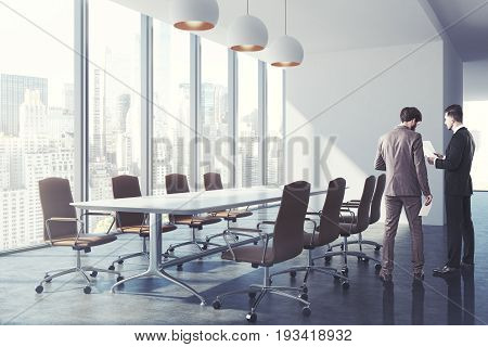 Men in a meeting room with a long white table surrounded by brown office chairs a panoramic window with a cityscape a row of ceiling lamps and a blank wall fragment. 3d rendering mock up