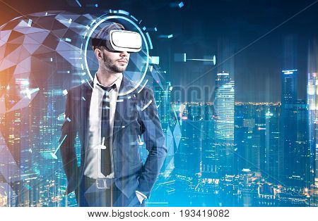 Front view of a bearded man wearing a suit and VR glasses and standing against a night cityscape. HUD and a globe hologram behind him. Toned image double exposure mock up