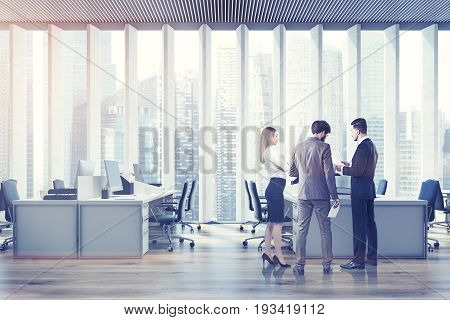 Business people in an open space office interior with a wooden floor a panoramic window with shades rows of computer tables and office chairs. Film effect. 3d rendering mock up toned image