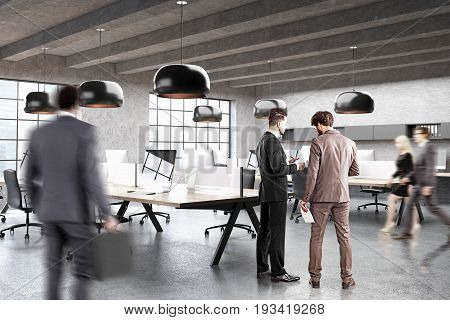 Modern open space office with concrete walls wooden floor and rows of tables with computers on them. Original lamps. Side view peope. 3d rendering mock up