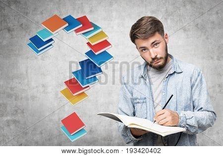 Portrait of a bearded young man in a jeans shirt. He is holding a black notebook and standing near a concrete wall with a question mark made of book.