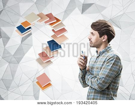 Side view of a bearded man with a marker wearing a checkered shirt and standing near a gray wall with a geometric pattern and a question mark made of book.