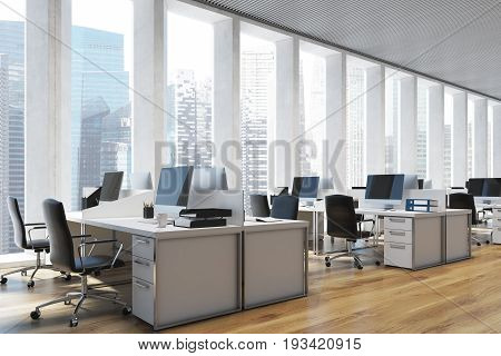 Side view of an open space office interior with a wooden floor a panoramic window with shades rows of computer tables and office chairs. 3d rendering mock up