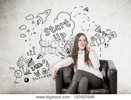 Young businesswoman with fair hair smiling and sitting in a leather armchair and talking on her smartphone. Concrete wall with a black start up sketch