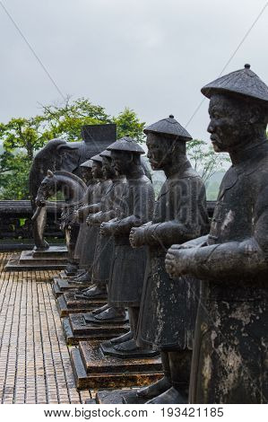 Statues of warriors in Imperial Khai Dinh Tomb in Hue Vietnam. Rainy day.