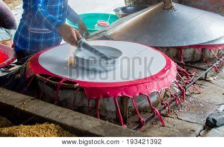 Cooking rice pancakes drying on the sun in the rice noodles factory Can Tho Mekong Delta South Vietnam